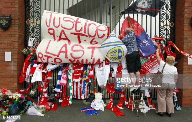 A man hangs a flag alongside other tributes placed on the Shankly Gates next to the Hillsborough Memorial at Liverpool's Anfield Stadium The...
