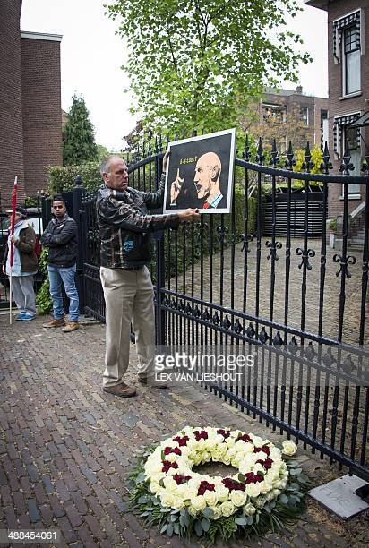 A man hangs a portrait on may 6 2014 inRotterdam of slain farright Dutch politician Pim Fortuyn near his former residence in his remembrance 12 years...