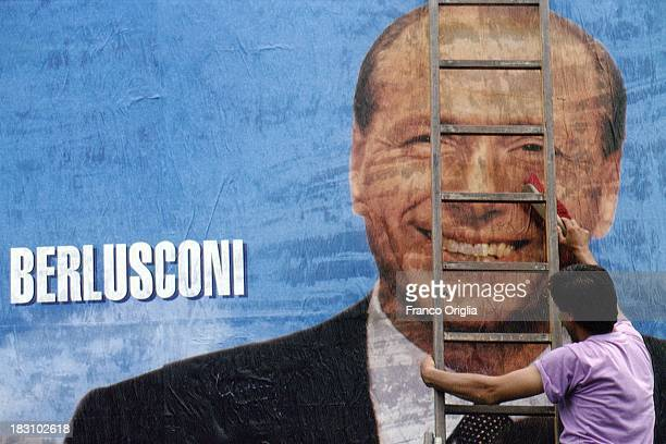 A man hangs a poster showing the face of Prime Minister Silvio Berlusconi for the European elections campaign on May 12 1994 in Rome Italy