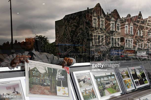A man hangs a property for sale sign in a shop front in Sydenham on October 8 2013 in London England The Government launched their 'Help to Buy'...