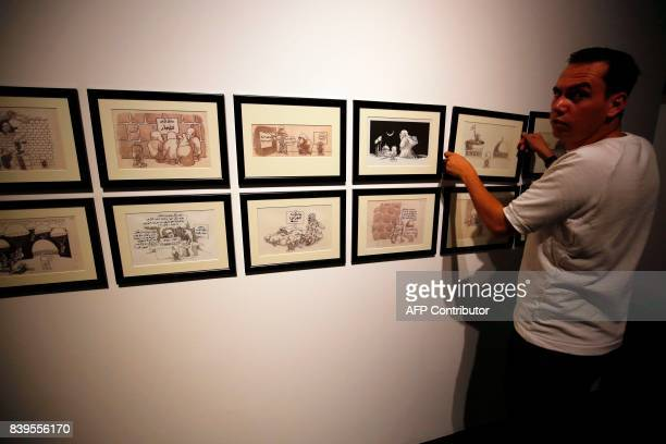 A man hangs cartoons by Palestinian caricaturist Naji alAli who was assassinated in London 22 July 1987 during a media tour ahead of the 'Jerusalem...