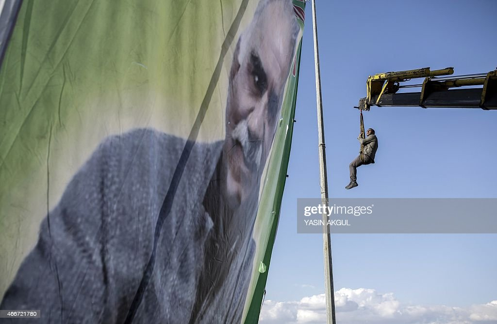 A man hangs from a crane while hanging a huge portrait of jailed Kurdish leader <a gi-track='captionPersonalityLinkClicked' href=/galleries/search?phrase=Abdullah+Ocalan&family=editorial&specificpeople=658599 ng-click='$event.stopPropagation()'>Abdullah Ocalan</a> as people gather for celebrations surrounding Newroz, which marks the arrival of spring and the new year, in Cizre, in Turkey's Sirnak province on March 18, 2015. AFP PHOTO / YASIN AKGUL