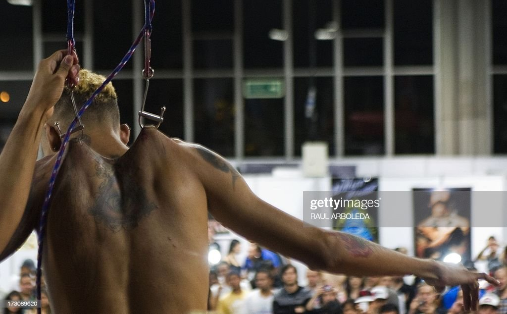 A man hangs from hooks put in his back and leg during the fourth International Tattoo Convention in Medellin, Antioquia department, Colombia on July 6, 2013. AFP PHOTO / Raul ARBOLEDA