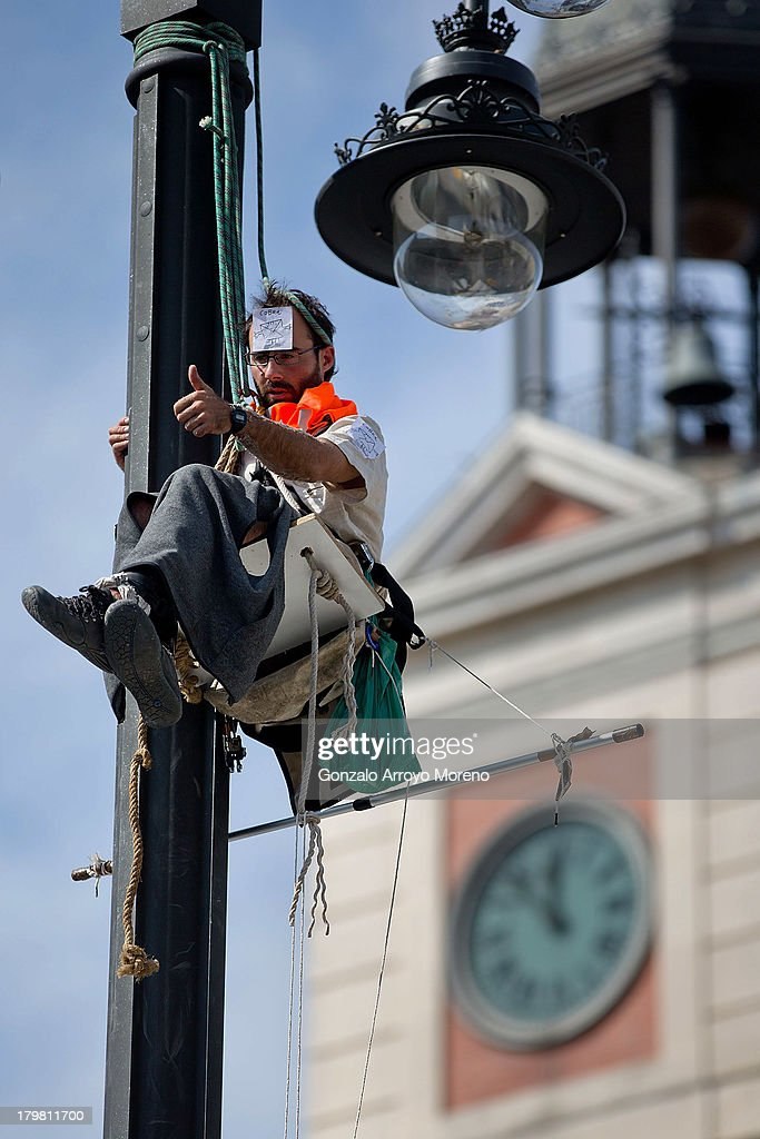 A man hangs in the air from a lampost as he protests against the Madrid 2020 Olympic Candidancy and Madrid City Council policy over evictions at Puerta del Sol on September 7, 2013 in Madrid, Spain.