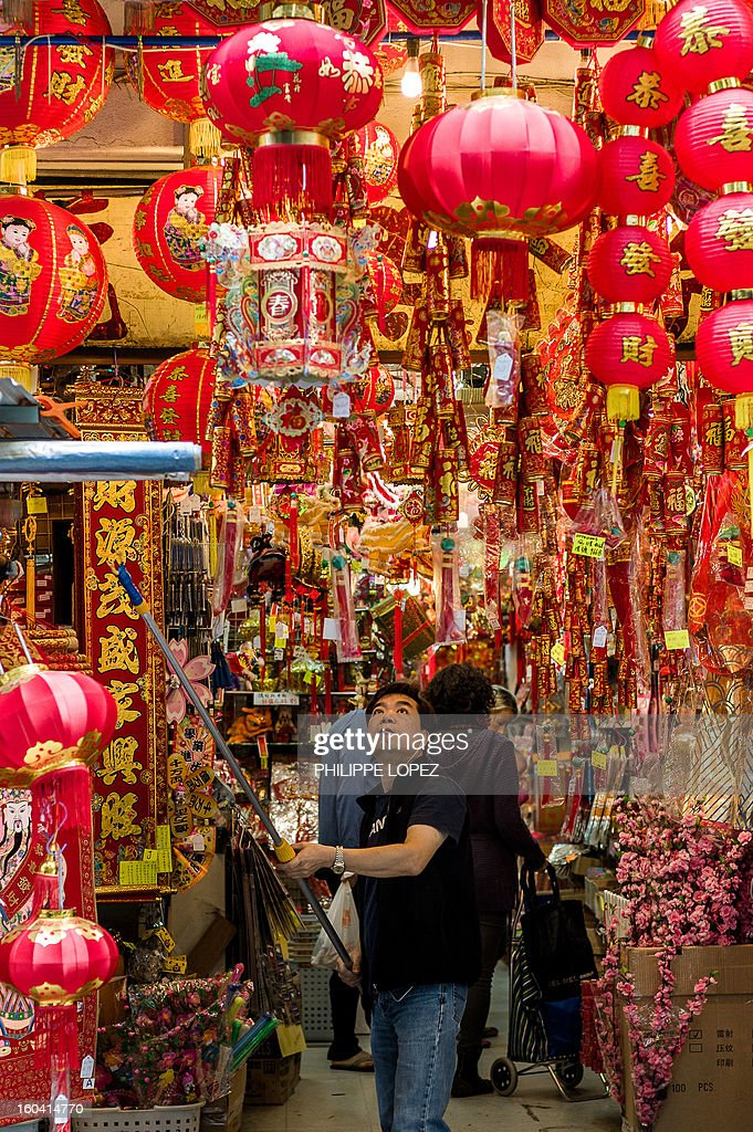 A man hangs lanterns in front of a store selling Chinese New Year items in Hong Kong on January 31, 2013. The Chinese New Year of the snake falls on February 10, 2013. AFP PHOTO / Philippe Lopez