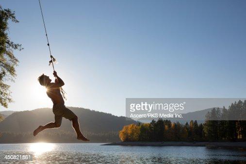 Man hangs onto rope swing above lake, hills