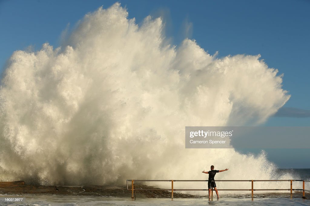 A man hangs onto the railing of North Curl Curl ocean pool after winds and rain battered Sydney last night producing large swell on January 29, 2013 in Sydney, Australia. Parts of Sydney are experienced record rainfall after ex-cyclone Oswald swept through the city last night.