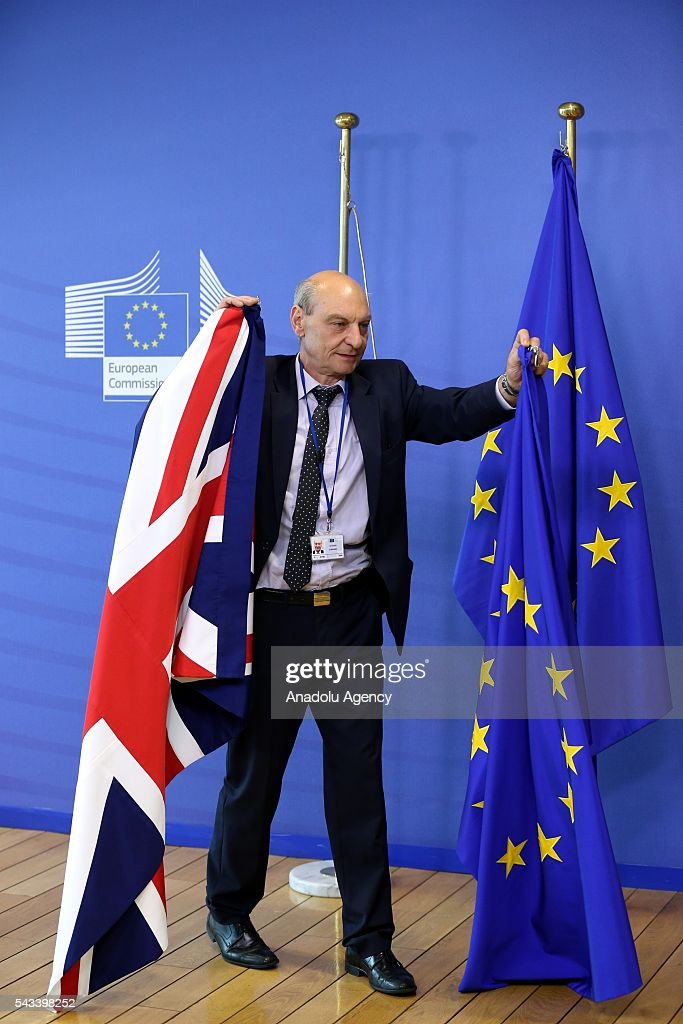 A man hangs the flag of the United Kingdom next to the European Union flag ahead of the meeting between British Prime Minister David Cameron and the President of the European Commission, Jean-Claude Juncker in Brussels, Belgium on June 28, 2016.