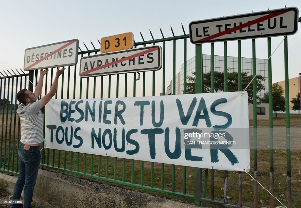 A man hangs village signs on the gate of the Lactalis factory next to a banner reading 'Besnier you going to kill us' as farmers block the access to...