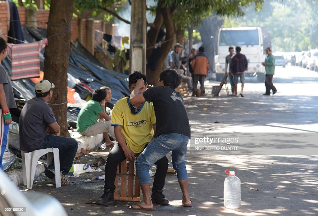 A man has a haircut in an encampment of natives of the Mbya ethnic group set in front of the Paraguayan Institute for the Natives (INDI) in Asuncion on May 31, 2016. The Mba are camped since 30 days ago demanding to the government to be granted the ownership of the 500 hectares of land they live in. / AFP / NORBERTO