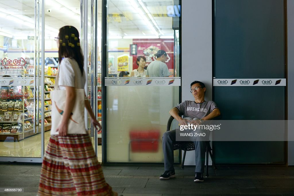 A man has a rest at the entrance to a shop in Beijing on July 13, 2015. China's total trade slumped in the first half of this year, official data showed on July 13, falling well short of the government's targets and dealing a blow to the global economy from its biggest trader in goods.
