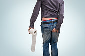 Man holding toilet paper roll and holding his butt on blue background. Diarrhea concept.