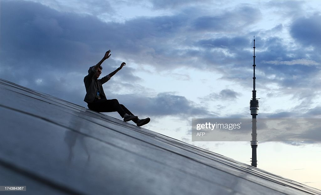 A man has fun sliding down along a metal surface of a monument in Moscow late on July 24, 2013 with Ostankino TV broadcasting tower in the backgrounds.