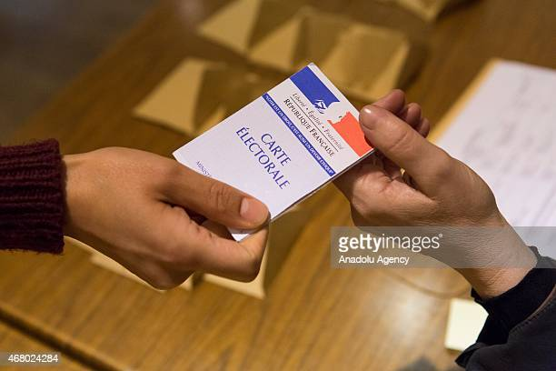 A man has his electoral card checked at a polling station during the second round of the French departmental elections in Meaux France on March 29...