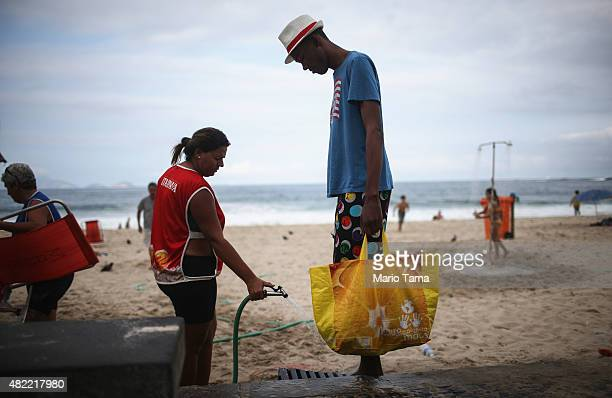 A man has his feet washed on Copacabana beach on July 28 2015 in Rio de Janeiro Brazil The famed beach will host various Olympic events including...