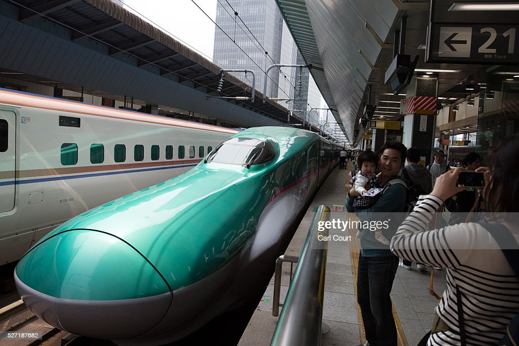 A man has his photograph taken with his daughter next to a Shinkansen bullet train at Tokyo Train Station on May 02, 2016 in Tokyo, Japan. The Shinkansen is a network of high-speed railway lines in Japan currently consisting of 2,764.6 km (1,717.8 mi) of lines with maximum speeds of 240-320 km/h (150-200 mph). The network presently links most major cities on the islands of Honshu and Kyushu, and Hakodate on northern island of Hokkaido. The maximum operating speed is 320 km/h (200 mph) though test runs have reached up to a world record 603 km/h (375 mph) for maglev trains in April 2015.