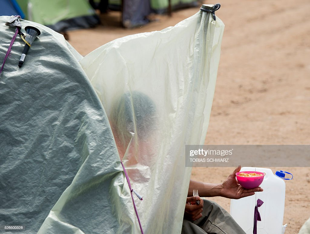 A man has lunch inside a tent at a makeshift camp for migrants and refugees near the village of Idomeni not far from the Greek-Macedonian border on April 30, 2016. Some 54,000 people, many of them fleeing the war in Syria, have been stranded on Greek territory since the closure of the migrant route through the Balkans in February. / AFP / TOBIAS