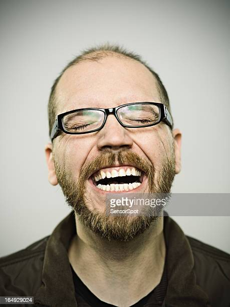 Man having a good laugh over gray background