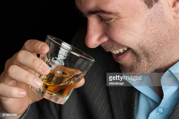 A man having a good time drinks whiskey from a glass