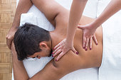 Man having a massage in a wellness center. Man relaxing on massage table receiving massage. Close-up of masseur's hands and a client's back. Young man is enjoying massage on spa treatment.
