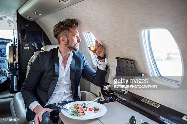 Mann mit einer Mahlzeit in einem privaten Flugzeug