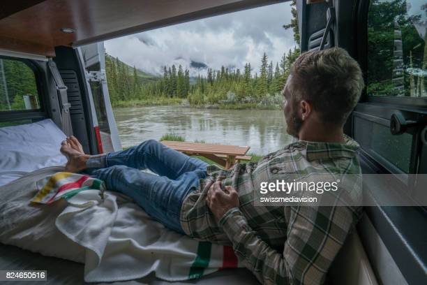 Man having a stunning view out of the back of his Camping Van