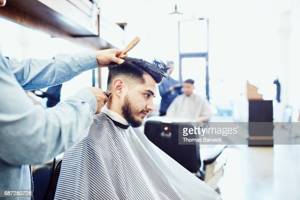 Man having back of neck trimmed during hair cut in barber shop