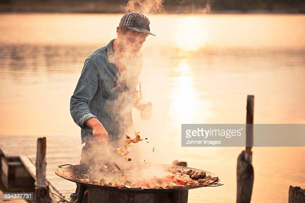 Man having barbecue at water