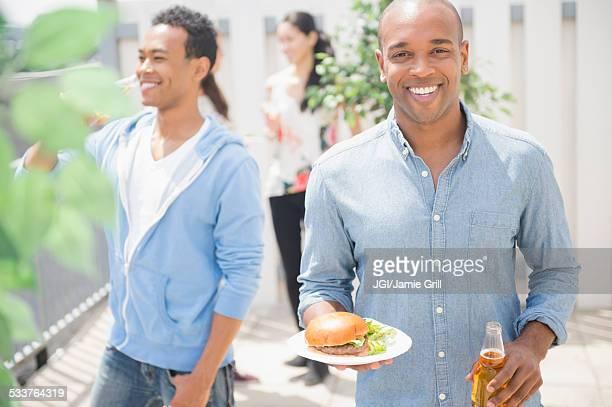 Man having beer and burger at backyard barbecue