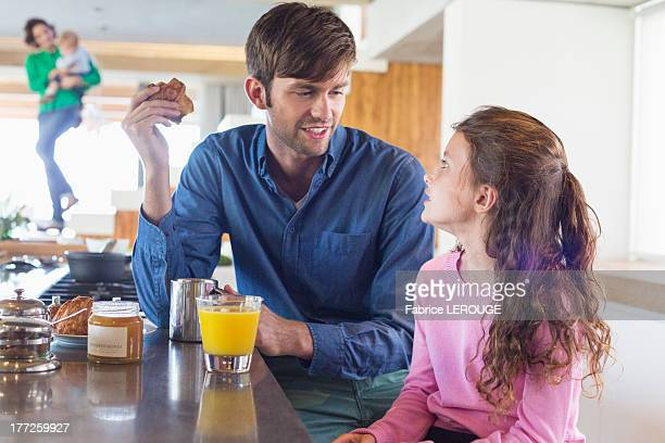 Man having breakfast with her daughter at a kitchen counter