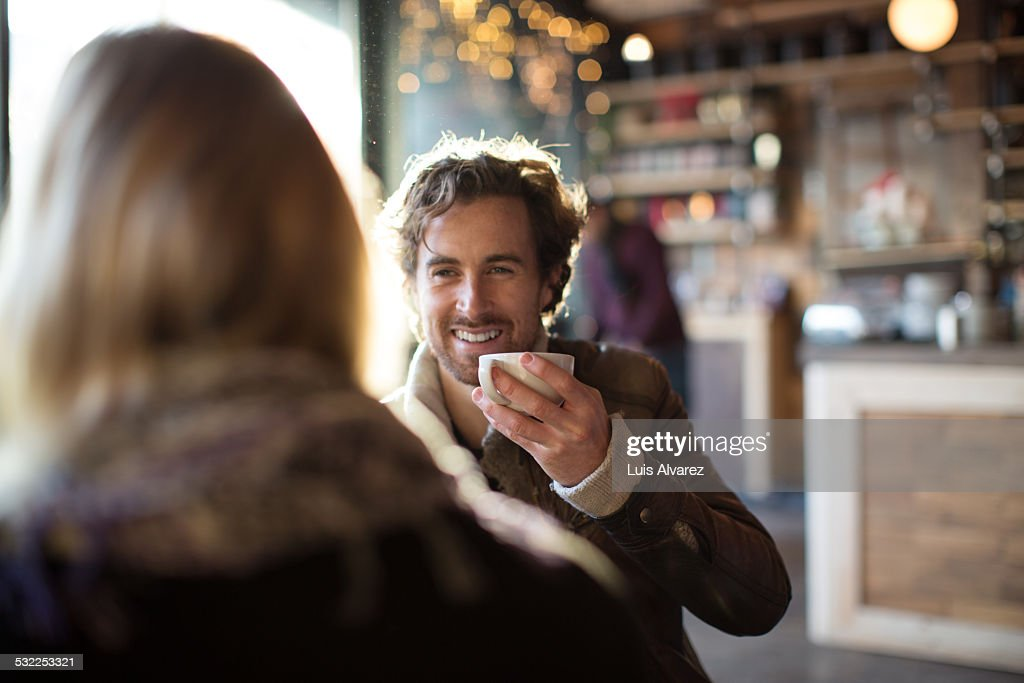 Man having coffee while looking at woman in cafe : Stock Photo
