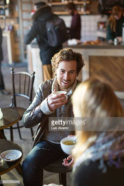 Man having coffee with female friend in cafe