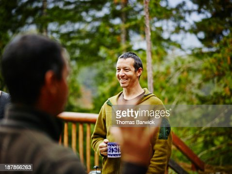 Man having coffee with friends on cabin deck : Stock Photo
