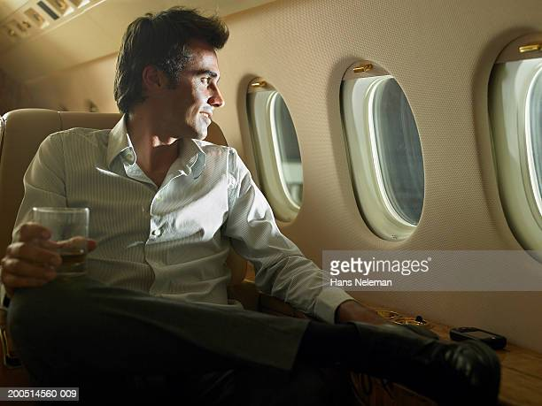 Man having drink on private plane