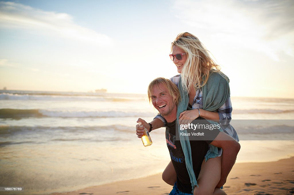 Man having girlfrien on the back on the beach : Foto stock