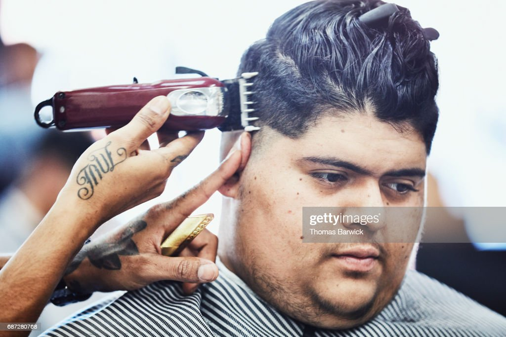 Man having hair cut with trimmers in barber shop : Stock Photo