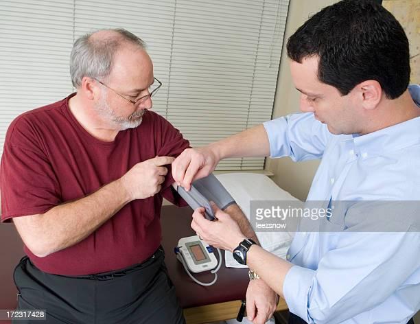 Mann mit seinen Blutdruck überprüft von Arzt mit Bündchen.