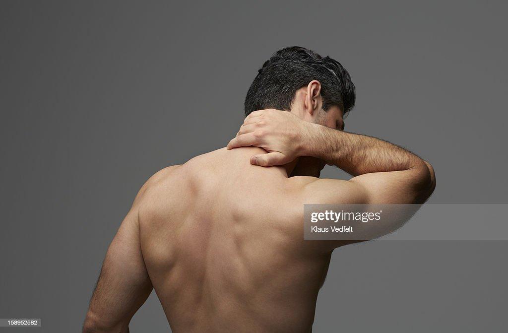 Man having neck pain (rear view)