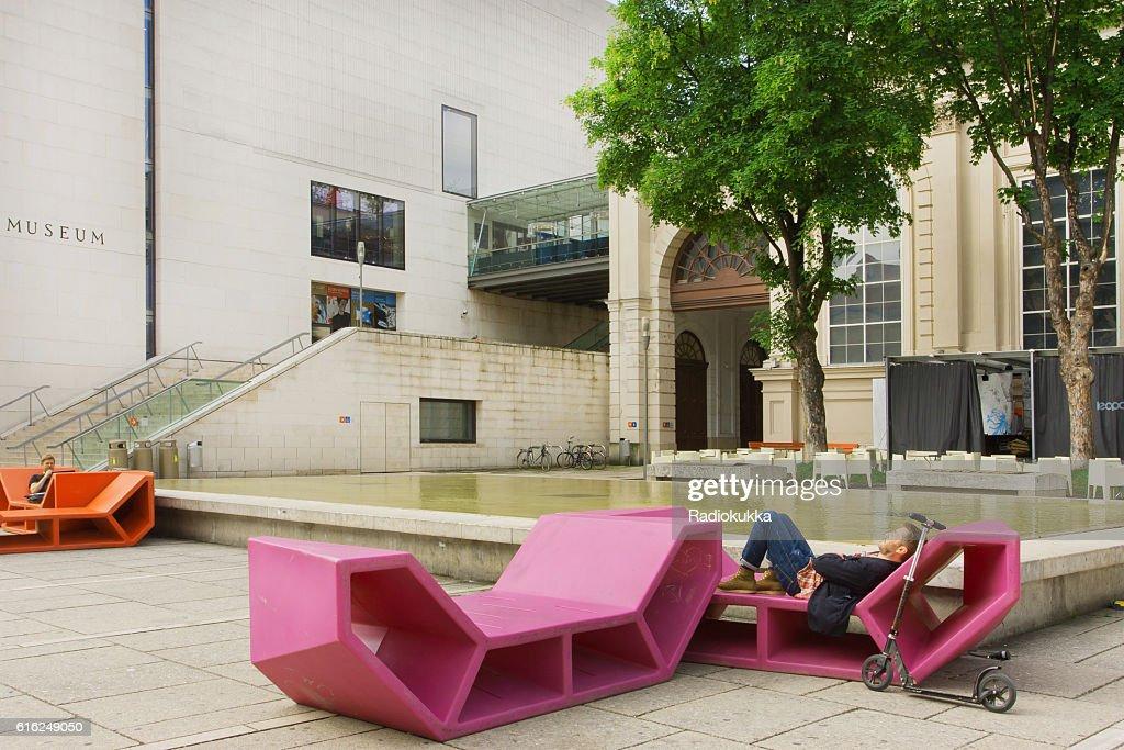 Man having rest in outdoor bench in modern style : Foto de stock