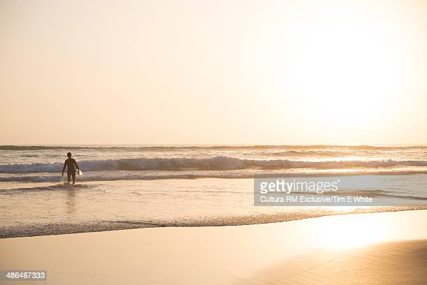 Man heading out to surf, Taghazout, Morocco