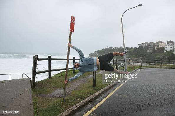 A man held by strong winds poses at Bondi beach on April 21 2015 in Sydney Australia A second day of damaging winds and heavy rain have hit the New...