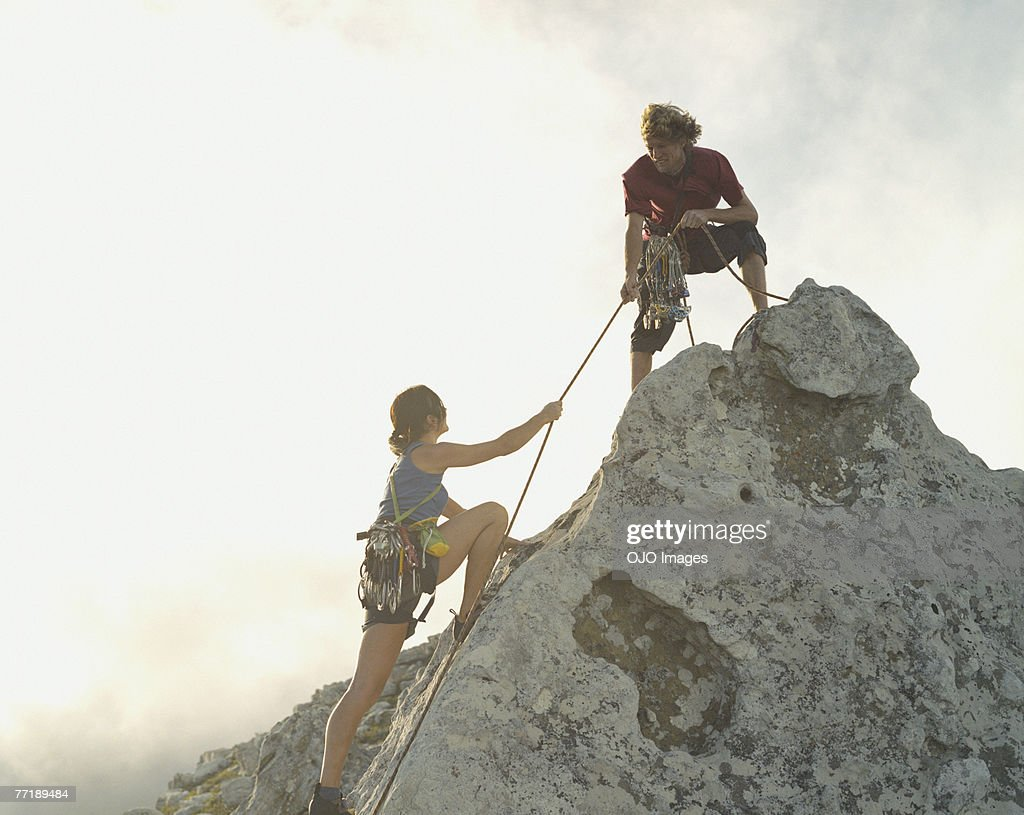A man helping a woman climber to the top of the mountain : Stock Photo