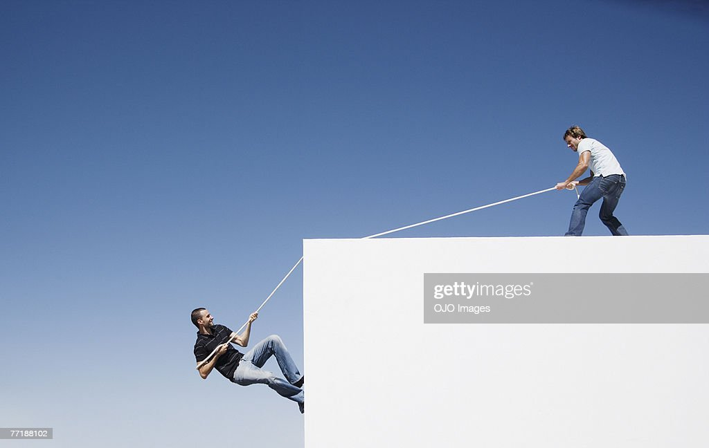 A man helping another man climb up a wall