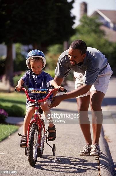 Man helping boy ride bike