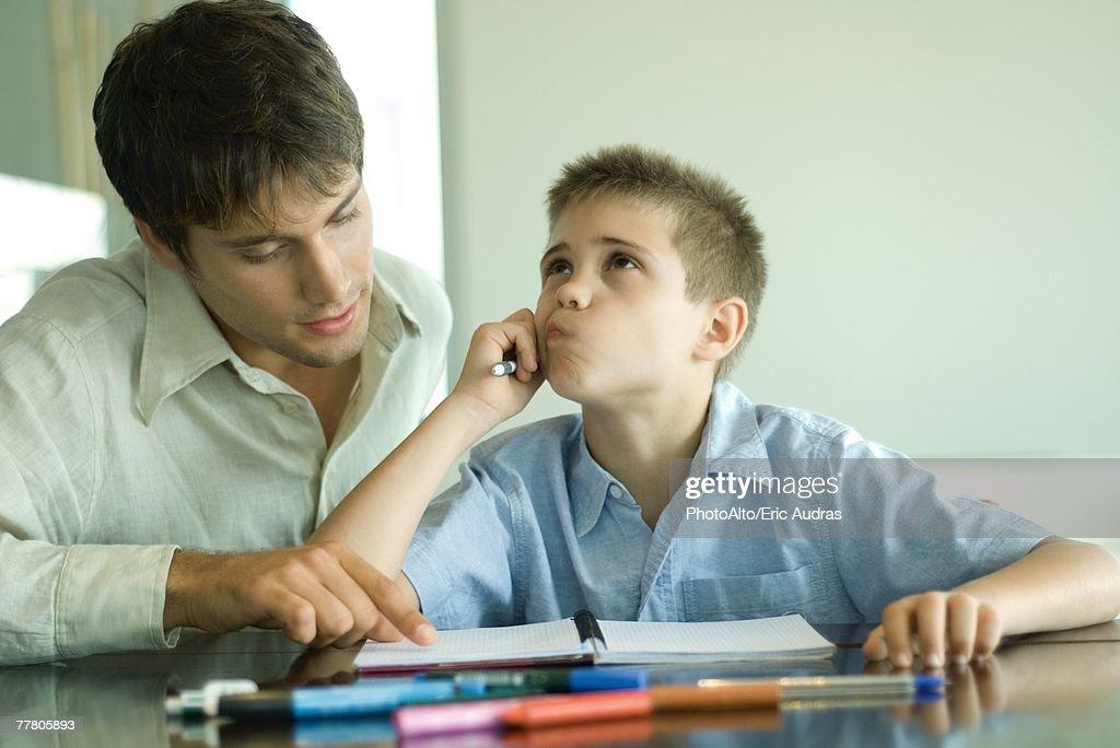 Man helping boy with homework