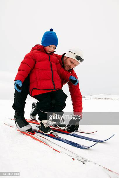 Man helping child put on skis in snow