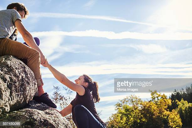 Man helping female friend to climb rock