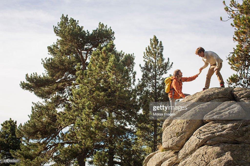 Man helping friend to climb rock