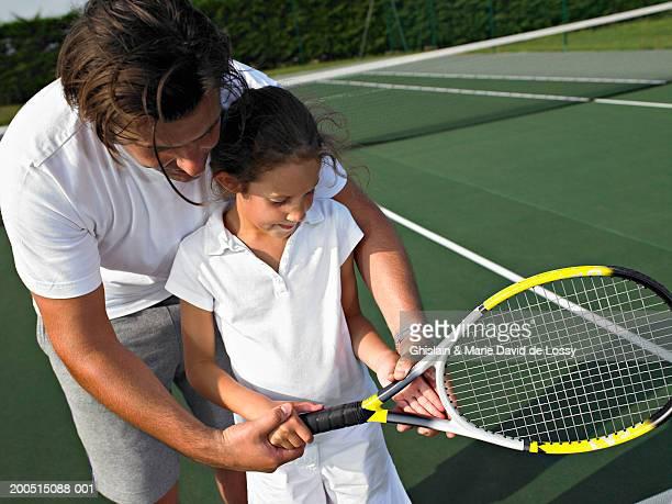 Man helping girl (6-8) hold tennis racket on court