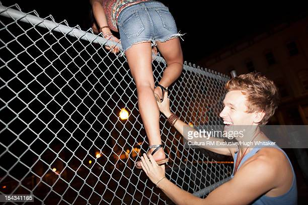 Man helping girlfriend climb fence